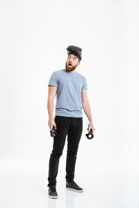 Image of young shocked man wearing virtual reality device look aside over white background.