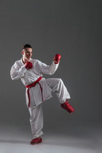 Image of young sportsman in kimono practice in karate isolated over grey background. Look aside.