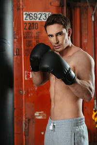 Image of young strong boxer posing in a gym near punchbag. Looking at camera.