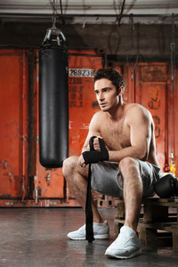 Image of young strong man sitting in a gym. Looking aside.