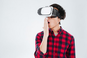 Image of young surprised asian man dressed in casual shirt in a cage and wearing virtual reality device. Isolated over white background.