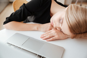 Image of young tired lady worker lies on table in office near laptop computer and sleeping. Eyes closed.