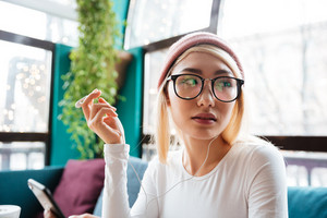 Image of young woman wearing hat and glasses listening music with earphones and looking aside in cafe.