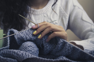 In the center of the image of a young girl's hand with bright manicure keeps knitting with spokes. The girl wearing a white sweater. Vintage photo. Close-up.