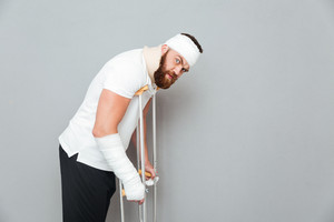 Injured bearded young man walking with crutches over white background
