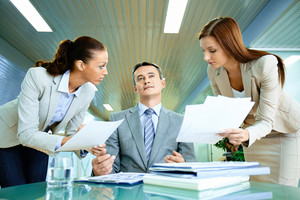 Inspirated boss sitting at workplace surrounded by two secretaries with papers