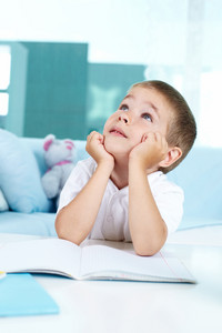Inspirated boy looking upwards while sitting by table