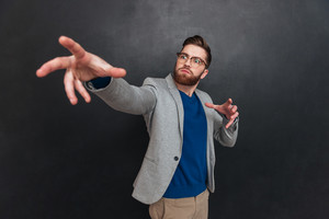Inspired bearded young businessman in glasses standing and pointing away