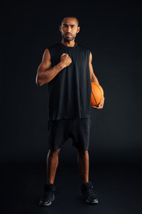 Intense serious sports man with basket ball holding hand on his chest isolated on a black background