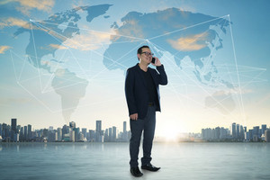 International business concept with businessman on city skyline background with network on map and sunlight