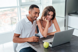 Interracial couple with laptop. sitting at the table