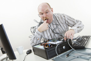 Irritated Businessman Licking Finger While Repairing Computer