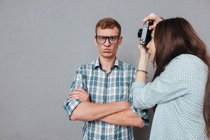 Irritated casual man in eyeglasses standing with arms folded while being photographed by a woman and looking at camera isolated on the gray background