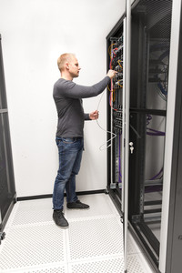 IT consultant installs network rack in datacenter