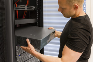 It engineer / consultant install / inserts a router / switch in a rack. Shot in a data center.