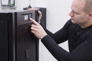 IT Engineer/ Consultant operate a large Uninterruptible Power Supply power in a datacenter.