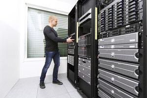 It engineer / consultant wokring and install / inserts a router / switch in a data rack. Shot in a data center.