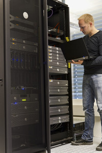 IT Engineer / Consultant working and monitoring systems and servers in a datacenter.