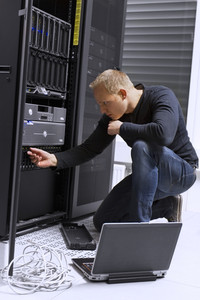 It engineer / consultant working in a data center. Changing hardrive in storage cabinet for SAN. Monitoring with a laptop.