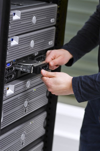 It engineer / consultant working in a data center. Install a new harddisk in a rack server.