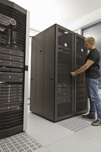 It engineer / consultant working in a data center. Opening a server rack door.