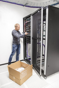 IT engineer installs network switch in datacenter