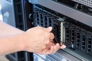 It engineer / technician working in a data center. Disk cabinet and servers.