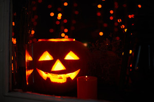 Jack-o-lantern and burning candle near by