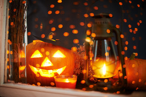 Jack-o-lantern with burning candles near by in a window