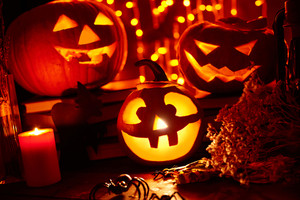 Jack-o-lanterns, burning candle and Halloween spiders in darkness