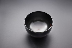 Japanese wooden black bowl on black background.