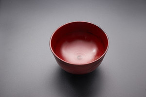 Japanese wooden red bowl on black background.
