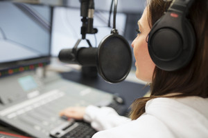Jockey Wearing Headphones While Using Microphone In Radio Studio