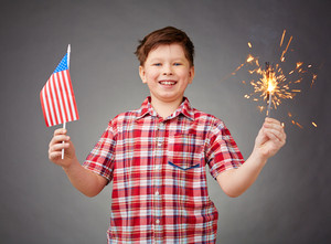 Joyful boy holding bengal light and American flag