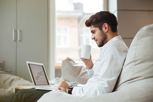 Joyful businessman dressed in white shirt sitting in cafe and drinking tea while looking at laptop.