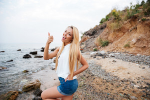 Joyful cute young woman winking and showing thumbs up on the beach