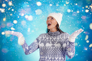 Joyful girl in winterwear enjoying snowfall