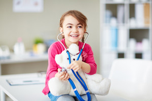 Joyful girl with teddybear using stethoscope in clinic