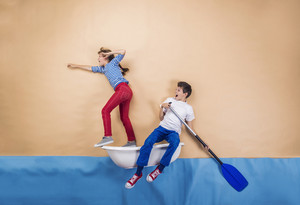 Joyful kids as sailors on the sea. Studio shot on a beige background.