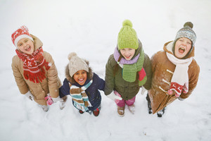 Joyful kids standing in snowdrift and looking at camera