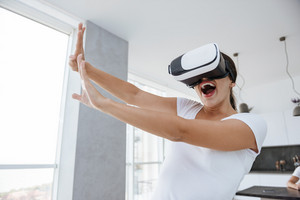 Joyful playful young woman playing computer games with virtual reality googles at home