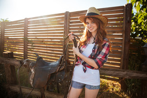 Joyful redhead young cowgirl preparing saddle for riding horse at ranch