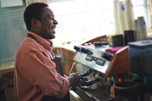 Joyful salesman making coffee on special equipment