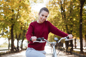 Joyful woman dressed in sweater walking with her bicycle outdoors. Look at camera.
