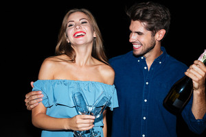 Joyful young couple holding glasses and bottle of champagne and laughing at night