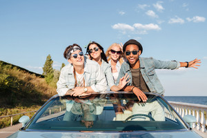 Joyful young friends having fun in cabriolet