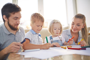 Kids and their parents with crayons drawing together at home