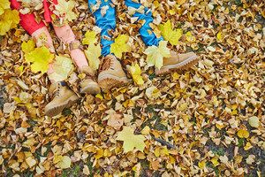 Kids legs in boots lying on autumn leaves