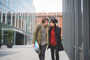 Knee figure of a couple of beautiful woman and man, with moustache and skate,walking through the streets of the city hugging and chatting- freshness, youth, carefreeness concept
