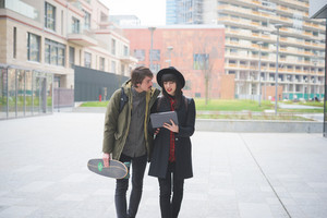 Knee figure of a couple of young beautiful woman and man, with moustache and skate, walking through the city using a tablet - technology, social network, communication concept